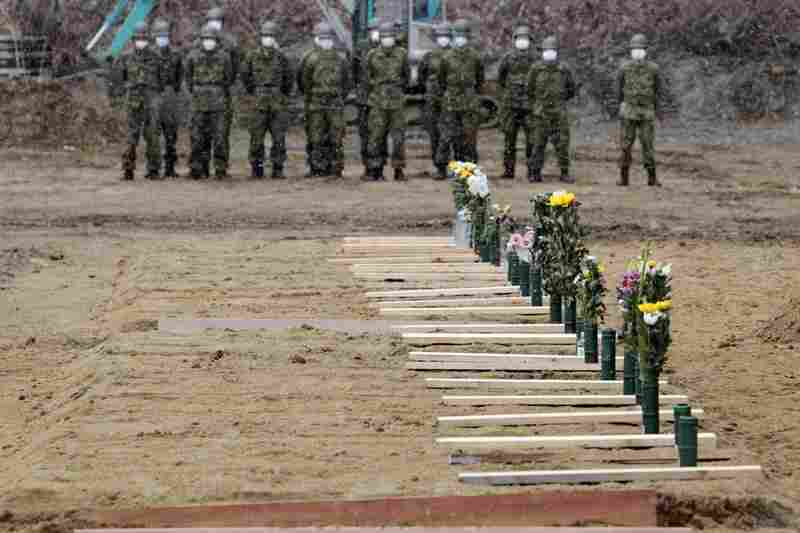 Japan Ground Self Defense Force troops stand near grave sites at a burial ceremony for the March 11 tsunami victims in Higashimatsushima city, Miyagi prefecture.