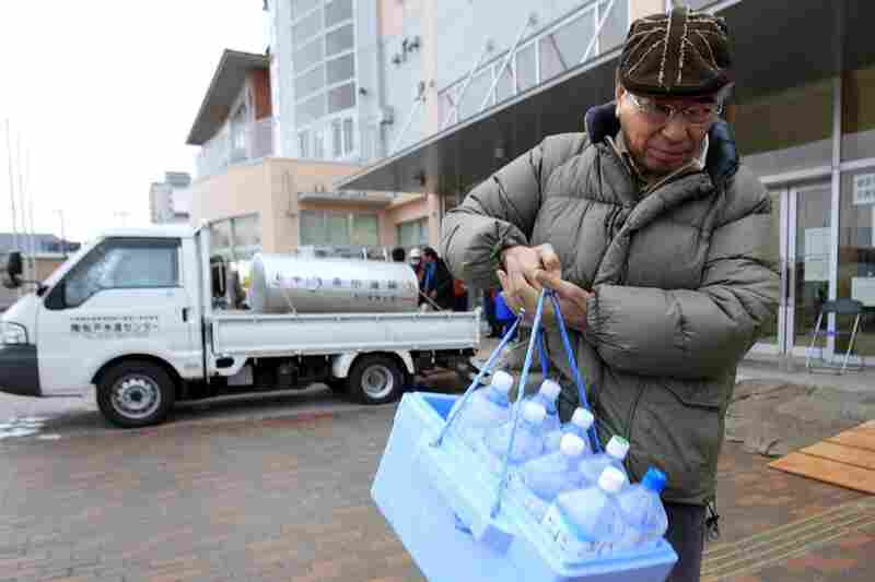 A man carries bottles of water after visiting a water tank in Urayasu, Chiba prefecture, near Tokyo. A spike in radiation levels in Tokyo tap water spurred new fears about food safety as rising black smoke forced another evacuation of workers trying to stabilize Japan's radiation-leaking nuclear plant.