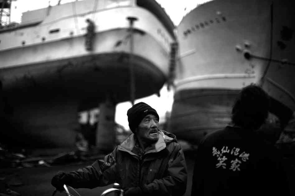 A man walks his bicycle between two boats washed ashore by the tsunami in Kesennuma.