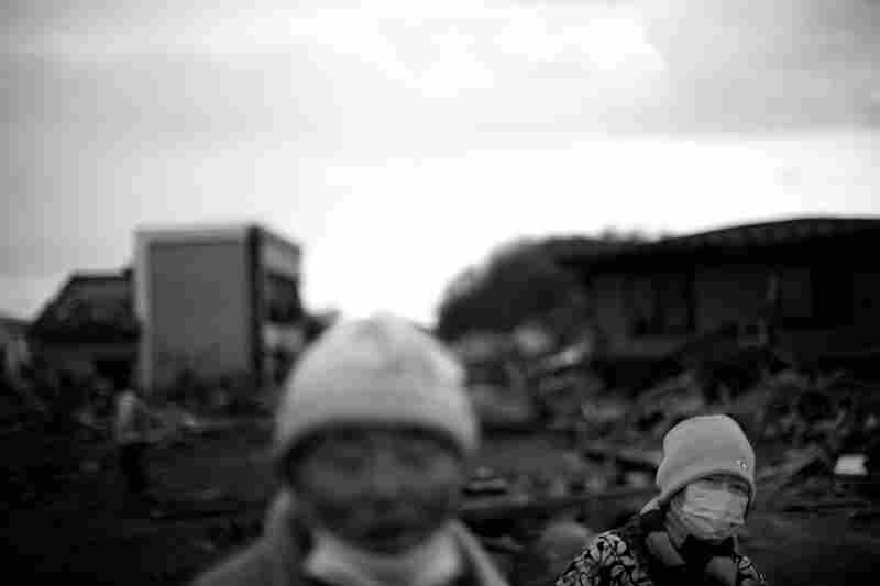 Hisayoshi Komatsu and his wife, Shoko, who are both retired from the fishing industry, walk through the ruins of the fishing docks.