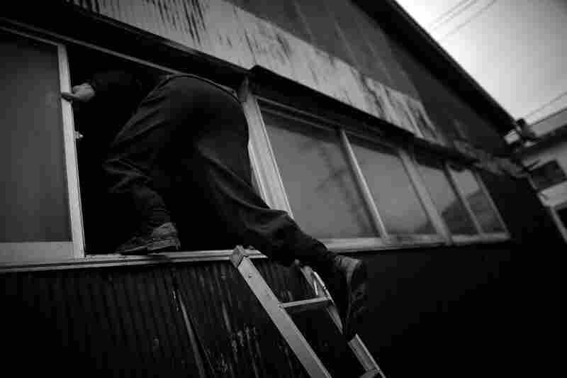 A man climbs through what was the third story window of his home in Kesennuma.