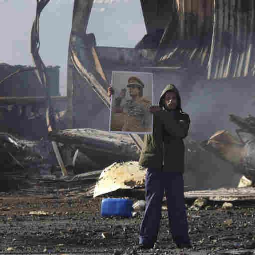 A Libyan supporter of Moammar Gadhafi stands amid the wreckage of what was described as a maintenance warehouse  at a naval base in Tripoli that was hit by coalition missiles.
