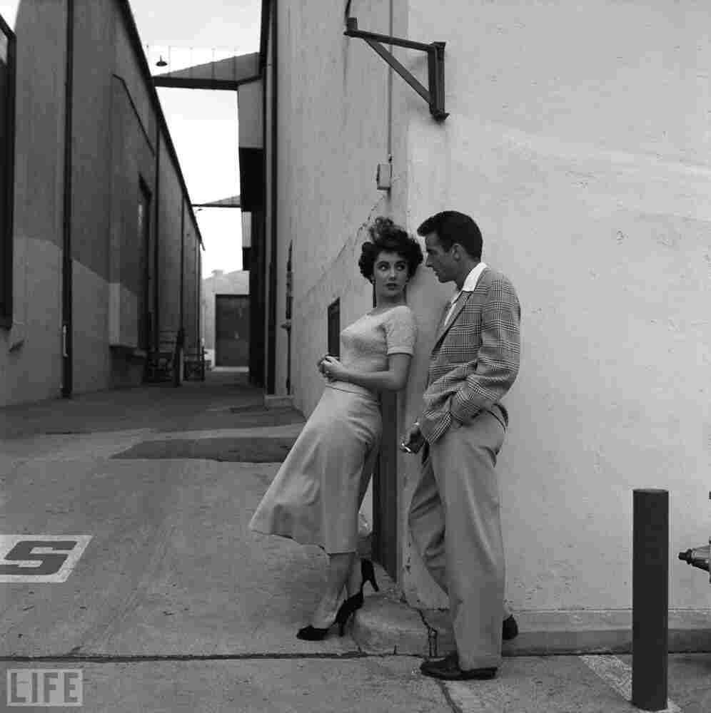 During a break in filming A Place in the Sun, Taylor chats with  her costar Montgomery Clift on the Paramount lot.