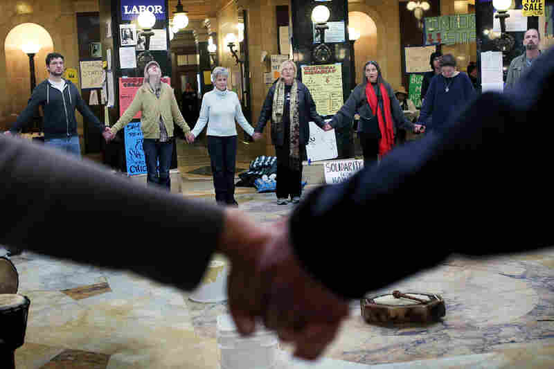 Protesters hold hands and chant in the Capitol rotunda on March 3 during around-the-clock demonstrations.