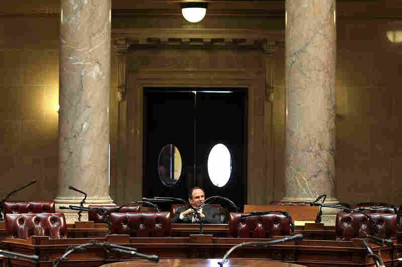 Chairs sit empty during a session of the state Senate at the Wisconsin State Capitol on Wednesday, where resolutions passed unanimously to impose $100-a-day fines on the 14 Senate Democrats who fled the state for each day that they do not show up for Senate sessions.