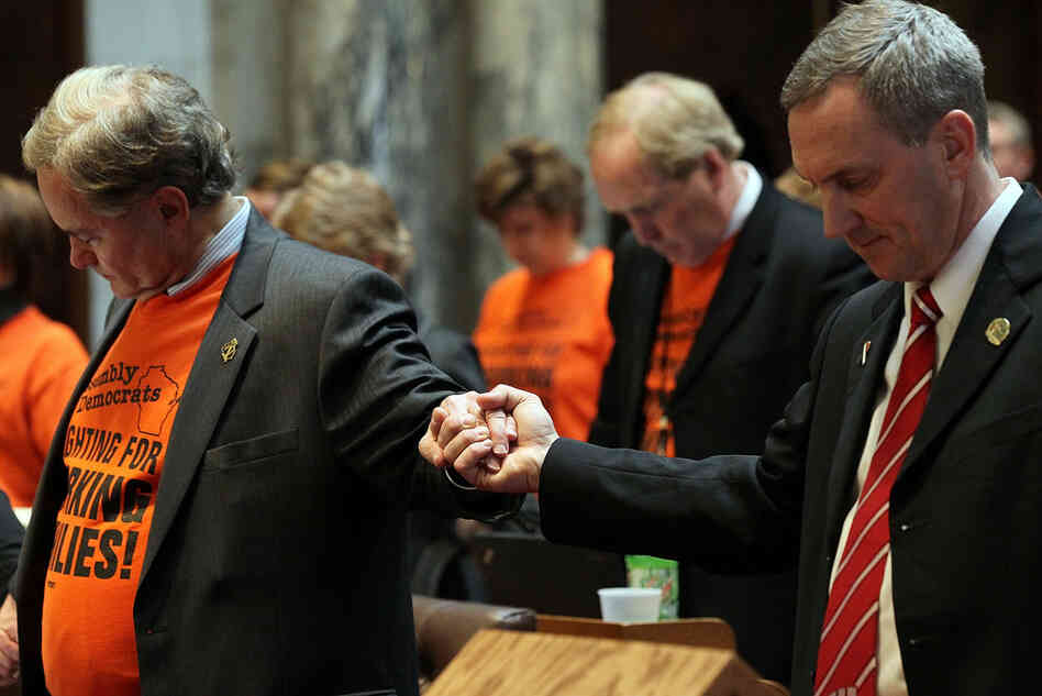 Democratic Assembly Minority Leader Peter Barca (left) holds hands with a Republican lawmaker during a prayer at the start of the Assembly session.