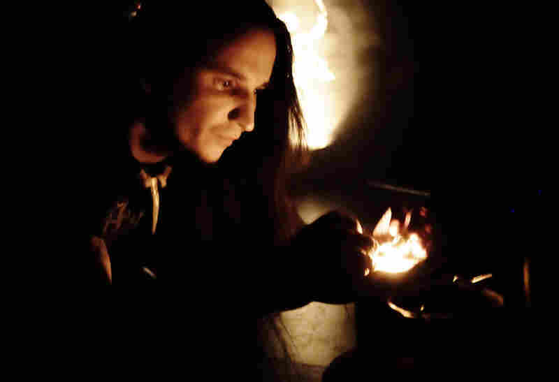 Guitarist and vocalist John Haughm lights incense at the front of the stage.