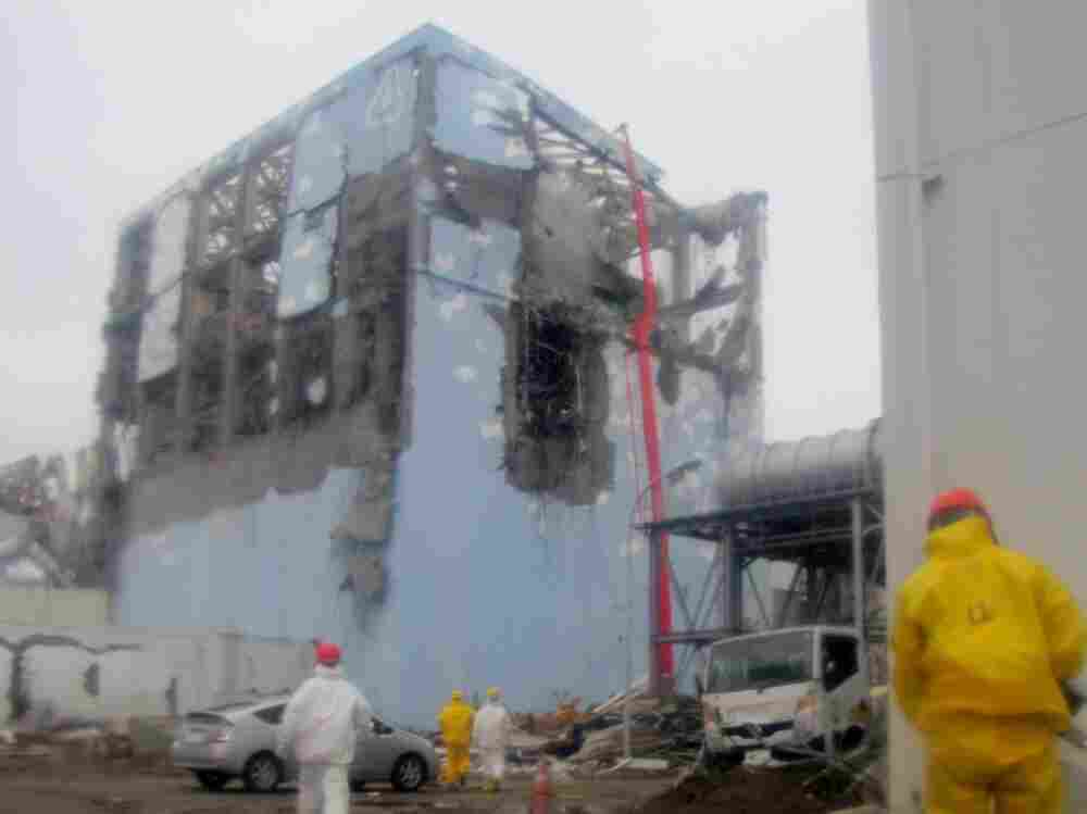 Workers in protective suits spray  water  at Unit 4. The building housing the reactor was badly damaged by fire and explosion.