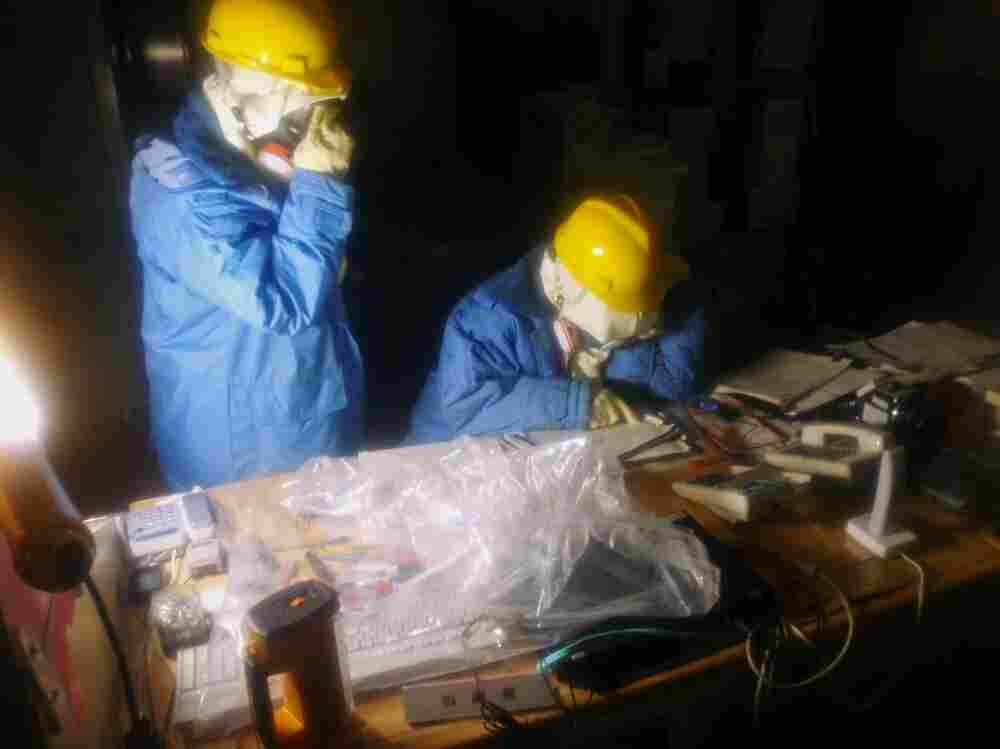 Workers collect data as part of an effort to repair a damaged reactor.