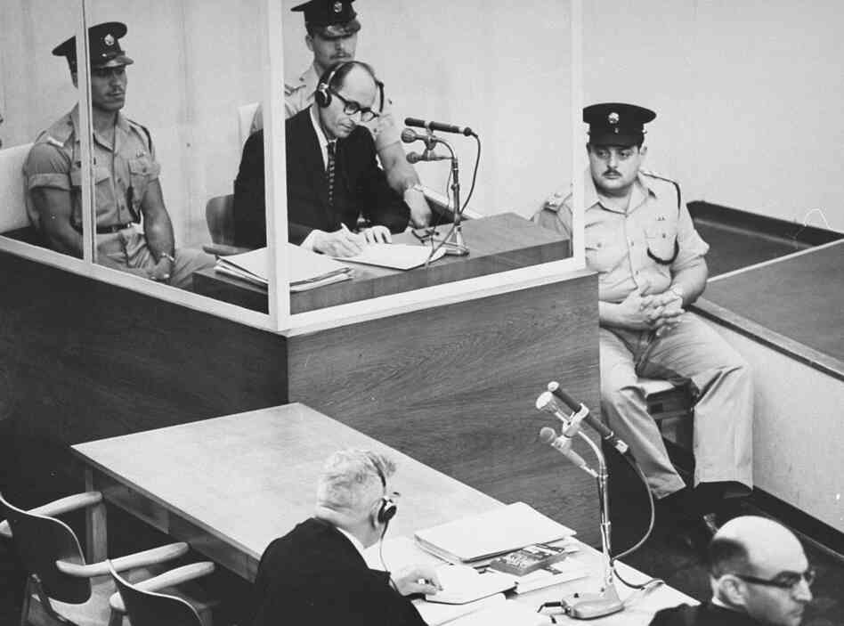 Defendant Adolf Eichmann takes  notes during his trial in Jerusalem.  The glass booth in which Eichmann sat was  erected to protect him from assassination.
