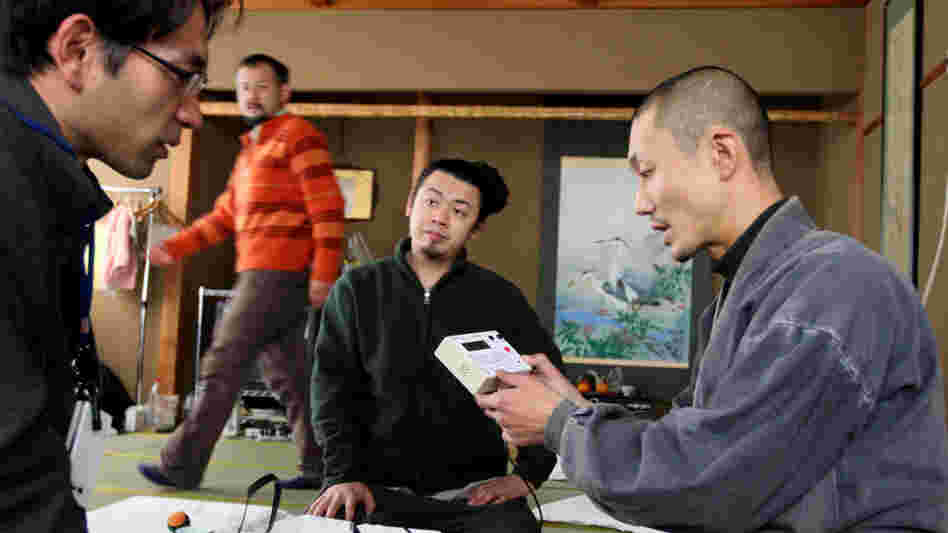 Japanese Buddhist monk Tanaka Tokuun, who was evacuated from Fukushima prefecture, looks over an instrument  measuring radiation levels at a hotel on March 17.