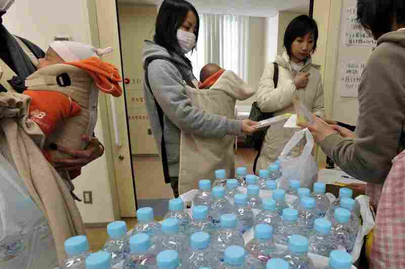 A mother holding her baby receives bottles of water at a Tokyo ward office Thursday after officials warned the day before that radioactive iodine over twice the safe level for infants had been detected in tap water. Wednesday's warning caused a run on bottled water, and the government is now asking people not to stockpile.