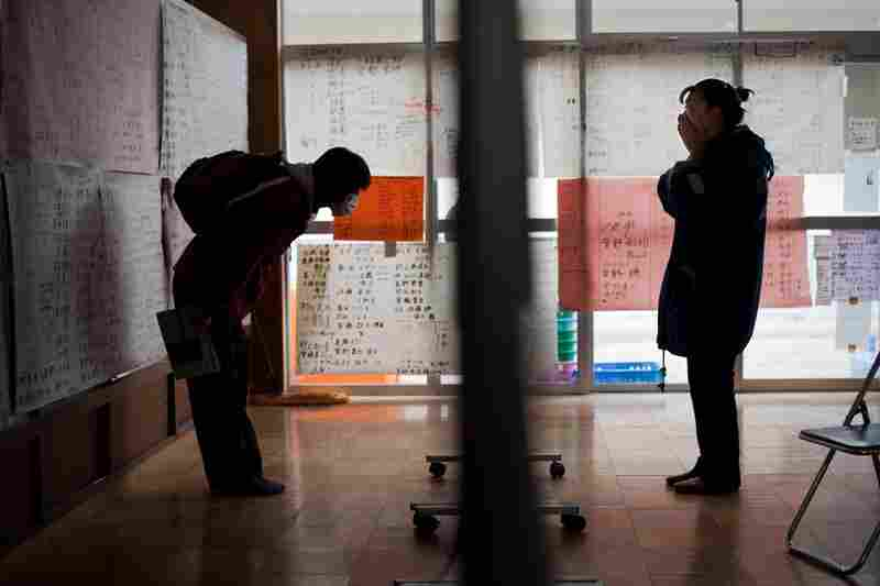 People read messages posted by survivors on the wall of a relief center in Rikuzentakata.