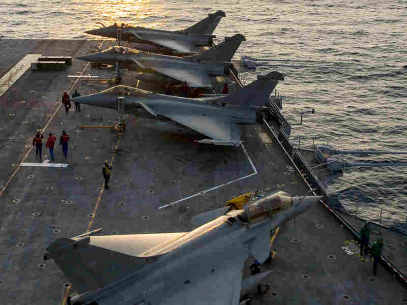 French jet fighters sit ready on the deck of the Charles de Gaulle aircraft carrier in the Mediterranean Sea.
