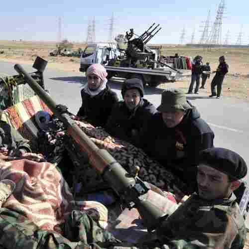 Libyan rebels rest in a pick-up truck near Ajdabiya, Libya on March 23, 2011 as government forces encircled the town.