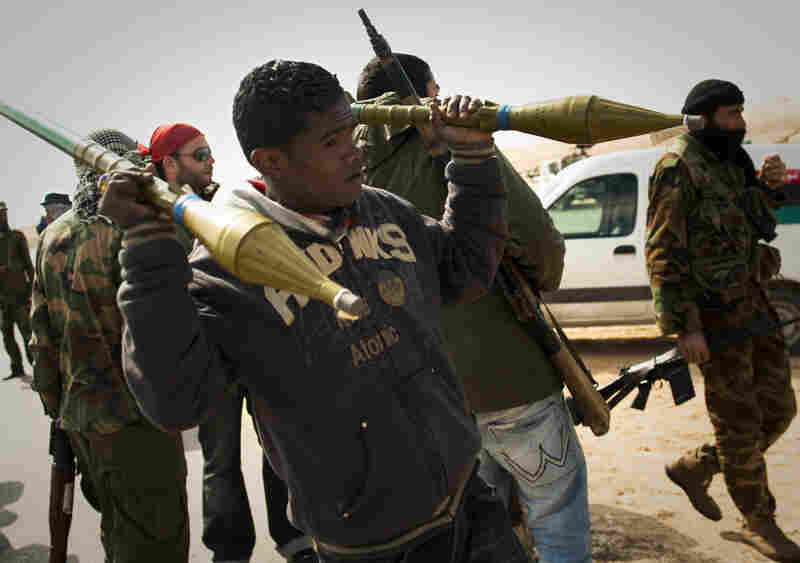 Rebels carry rockets on a checkpoint on the front line near Zwitina, the outskirts of the city of Ajdabiya, south of Benghazi, eastern Libya, on March 24.