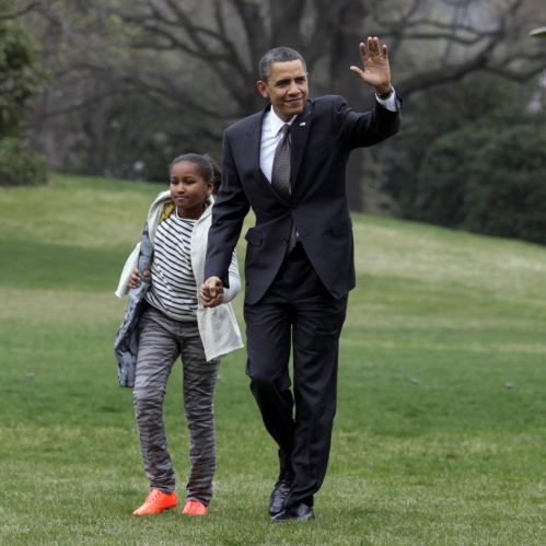 President Barack Obama walks across the White House's South Lawn with his family, returning from a Latin American trip on Wednesday, March 23, 2011.