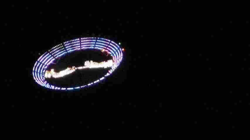 "US plastic artist Peter Coffin's ""Flying Saucer"" — a 7-meter, LED-studded, SMS-controlled flying saucer and lifted by a helicopter — overflies Ipanema beach, on May 23, 2009, in Rio de Janeiro, Brazil."