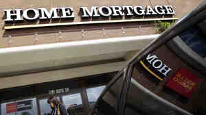 A woman walks past a Wells Fargo Home Mortgage office in La Habra, Calif. Many mortgage brokers say the Federal Reserve's new rules favor big banks.