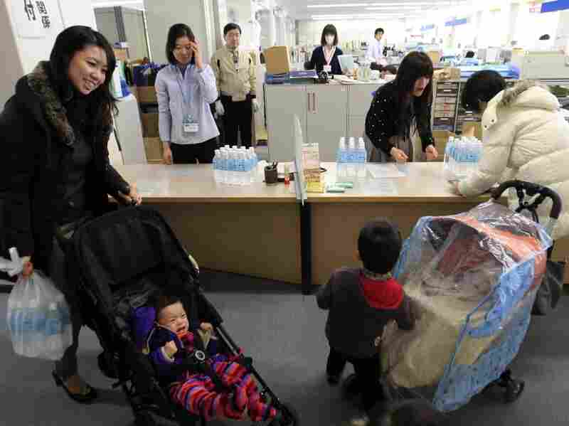 Mothers receive bottled water at a ward office in Tokyo, Friday, March 25, 2011 as the Tokyo Metropolitan Government started on Thursday to distribute three small bottles of water each to an estimated 80,000 families with babies of 12 months or younger.