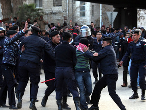 Jordanian police arrest a government supporter after clashes Friday with protesters in Amman, Jordan. Pro-government forces threw stones at demonstrators demanding the dissolution of parliament and the firing of the country's prime minister. Six people were hurt.