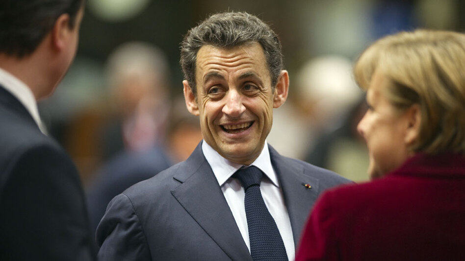 French President Nicolas Sarkozy talks with German Chancellor Angela Merkel and British Prime Minister David Cameron on Friday.