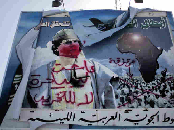 A vandalized billboard of Gadhafi stands outside the airport of the eastern city of Benghazi.
