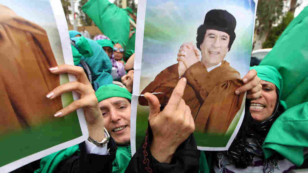 Libyan women hold pictures of leader Moammar Gadhafi in Tripoli earlier this month during a protest against the U.N. resolution authorizing a no-fly zone. The government, says NPR's David Greene, wants Tripoli to seem like a place full of people who revere Gadhafi. There are signs, however, that Gadhafi's grip on the capital could be loosening.