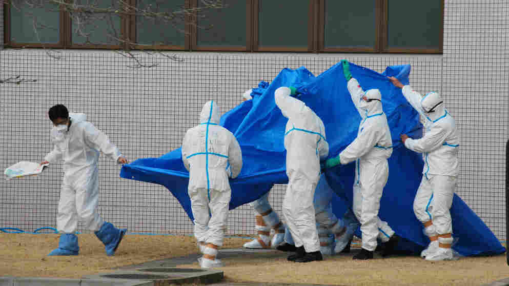 Officers in radiation protection suits hold a blue sheet over patients who were exposed to radiation at the Fukushima complex as they're taken to the hospital.