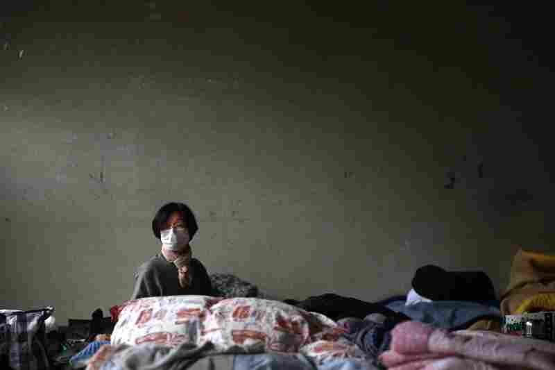 A woman sits in an empty corner of a shelter for residents who have been evacuated from the region near the damaged Fukushima nuclear plant, in Soma, Fukushima prefecture, northeastern Japan.