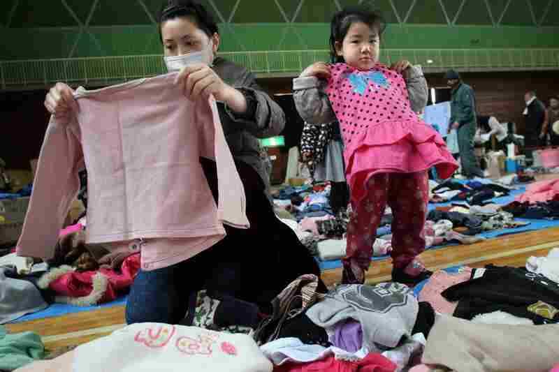 A girl and her mother inspect donated clothes at a shelter in Onagawa.