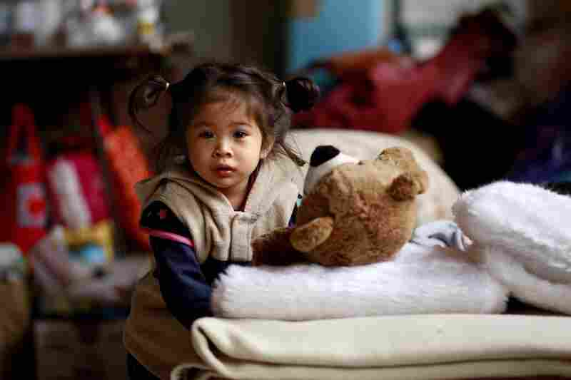 A young girl plays with a teddy bear at an evacuee center in Soma.