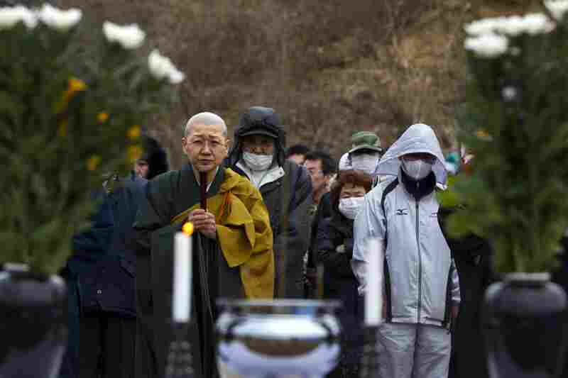 Mourners pray during a memorial ceremony at a temporary burial site in Higashi-Matsushima, Miyagi prefecture. Japanese Buddhists traditionally cremate the dead, but with the death toll so high, crematoriums are overwhelmed. There is also a shortage of fuel for cremations.