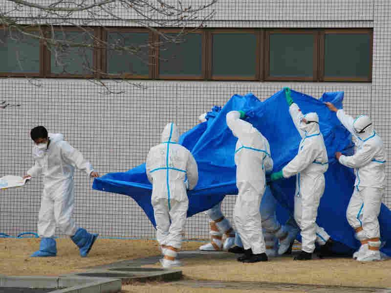 Japan Self-Defense Force officers in radiation protection suits hold a blue sheet over patients who were exposed high levels of radiation at the the Fukushima nuclear power plant as they are transferred to a hospital Thursday.