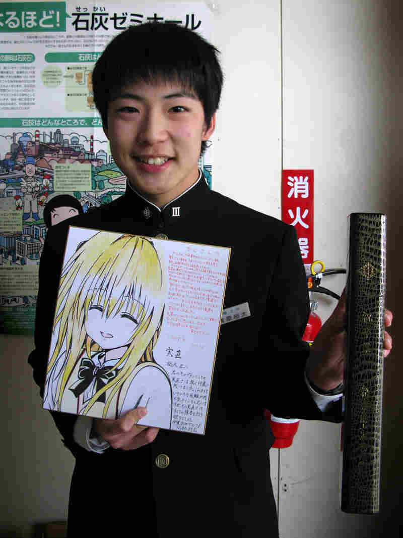 Yuta Kajiwara holds his junior high school diploma and a large graduation card given to him by members of his volleyball club. One of his classmates was killed in the tsunami and two remain missing. Kajiwara says he has known the victims since grade school.