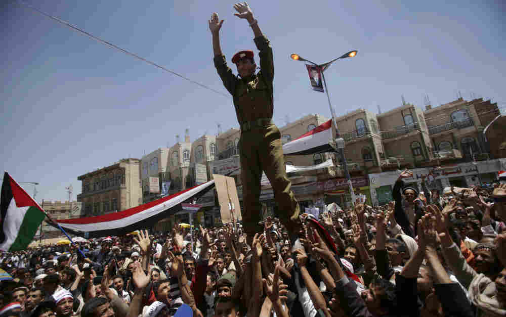 A Yemeni army officer is lifted by anti-government protestors in a demonstration against President Ali Abdullah Saleh, in Sanaa, Yemen, Thursday, March 24, 2011.