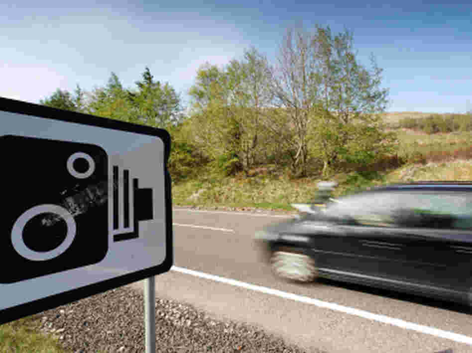 A car passes a warning sign for speed cameras.