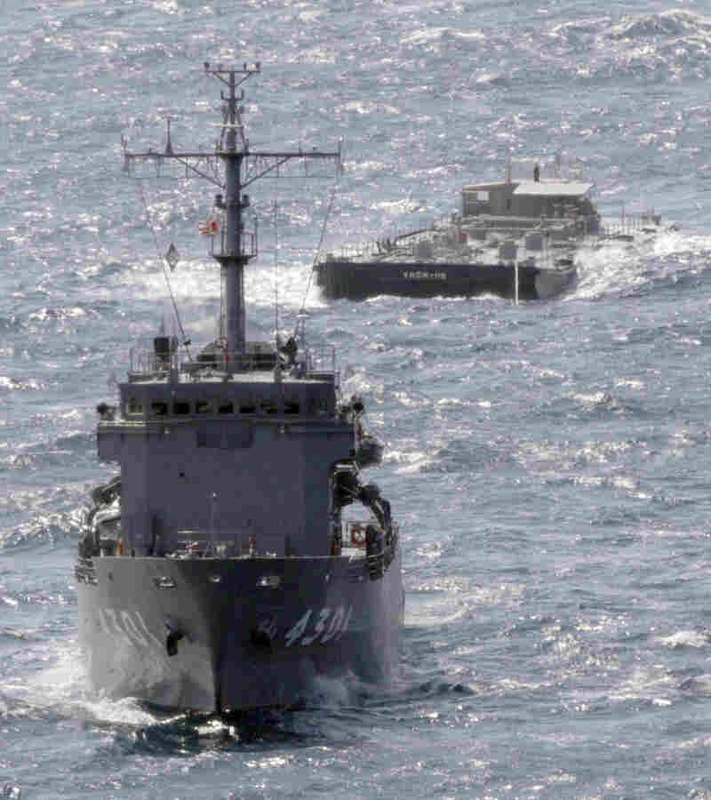 A U.S. Navy barge, back, is towed Saturday by a Japanese Maritime Self-Defense Force support ship off the coast of Japan. The barge is carrying 275,000 gallons of freshwater to support cooling efforts at the damaged Fukushima Dai-ichi nuclear power plant.
