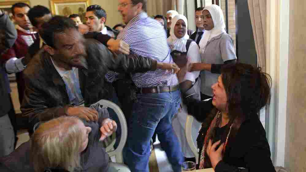 A Ministry of Information official, left, tries to grab Iman Al-Obeidi,  who said she spent two days in detention after being arrested at a  checkpoint in Tripoli  and was sexually assaulted by up to 15  men while in custody.