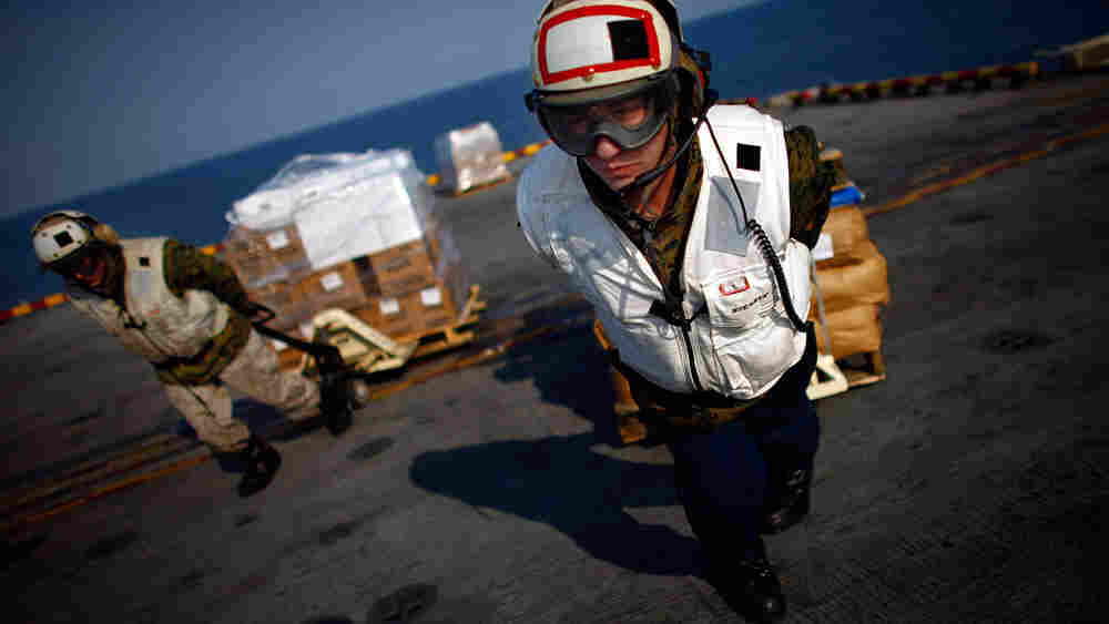 Marine Lance Cpl. Gregory Pollina pulls a pallet of relief supplies to a waiting helicopter aboard the USS Essex, which is conducting operations in support of Operation Tomodachi. The  Marines and Navy are flying the much needed aid to the tsunami-devastated northeast coast of Japan.