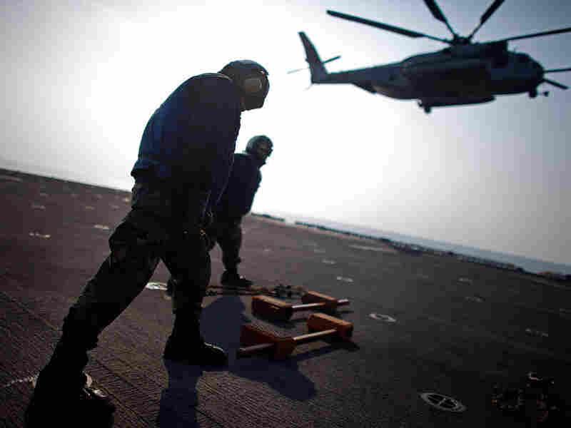 Crew members aboard the USS Essex brace against the rotor wash from a Marine helicopter that is also taking part in Operation Tomodachi.
