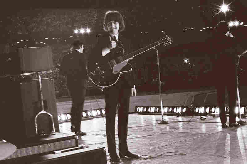 From the stage at Metropolitan Stadium in Bloomington, Minn., George Harrison turns to see Bob Bonis with his camera and gives him a thumbs up. Aug. 21, 1965.