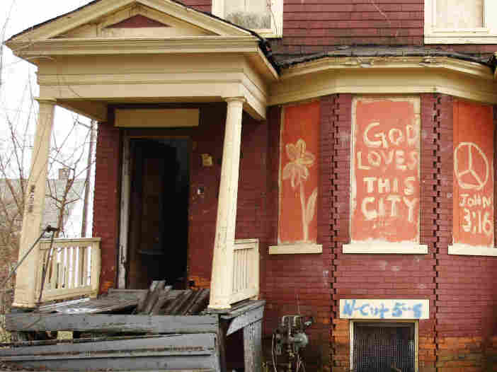 """The words, """"God Loves This City"""" are painted on the front of an abandoned home in Detroit."""