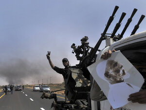 Libyan rebels pushed westward from the town of Bin Jawad toward Moammar Gadhafi's hometown of Sirte on Monday.