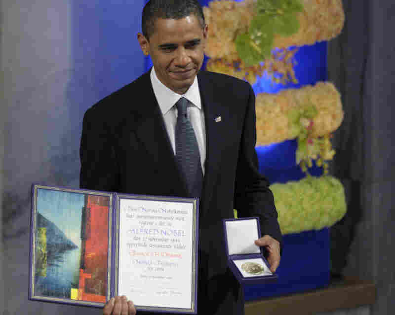 "President Obama displays his Nobel Peace Prize during a ceremony in Oslo in December 2009. During his acceptance speech, the president discussed the concept of a ""just war,"" saying: ""There will be times when nations — acting individually or in concert — will find the use of force not only necessary but morally justified."""