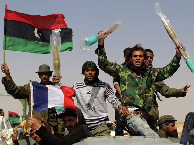 Libyan rebels, waving the French and rebellion flags, raise brand new rocket propeled grenades they took from abandonned pro-government forces ammunitions stocks on March 27, 2011 in Ajdabiya.