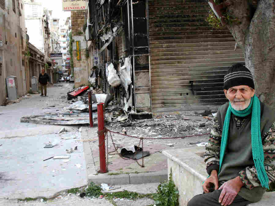 An elderly man sits near a burnt-out building in Latakia on March 27, 2011.