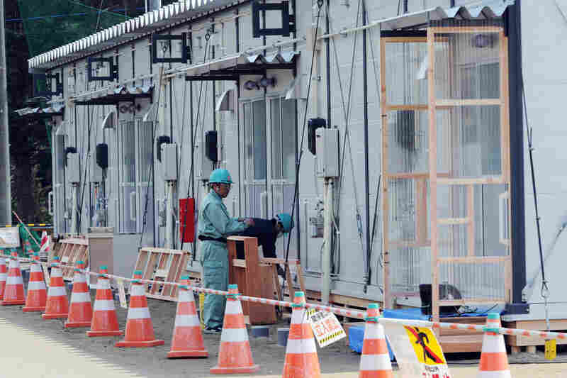 Construction workers build temporary houses on the grounds of a junior high school in Rikuzentakata. Some 36 houses will be prepared in April.