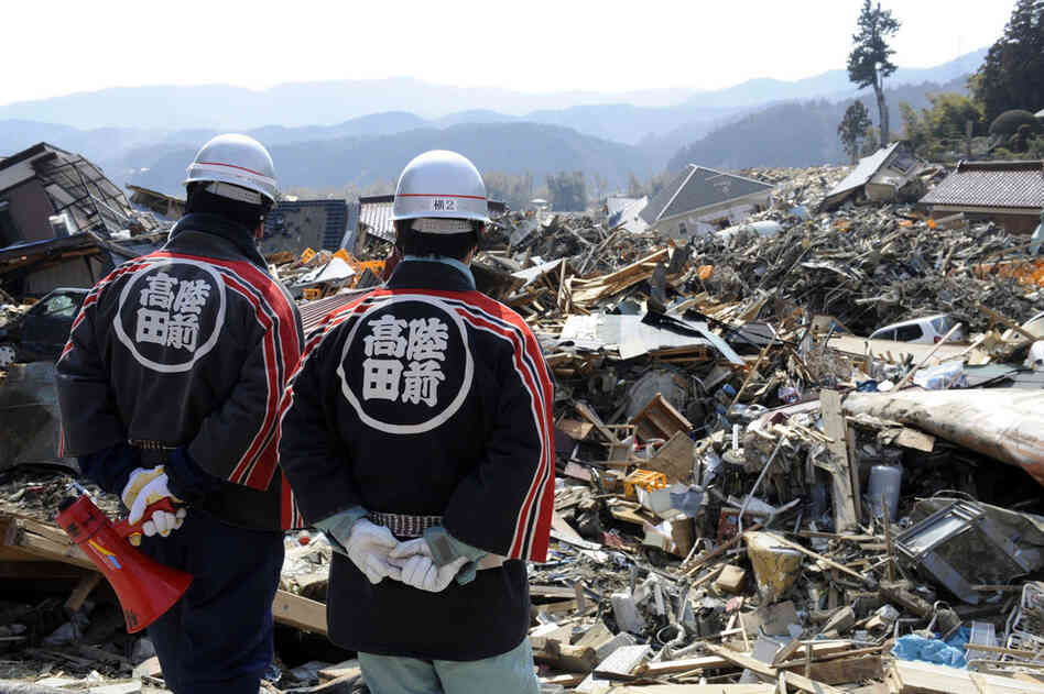 Local firefighters look at debris in Rikuzentakata.
