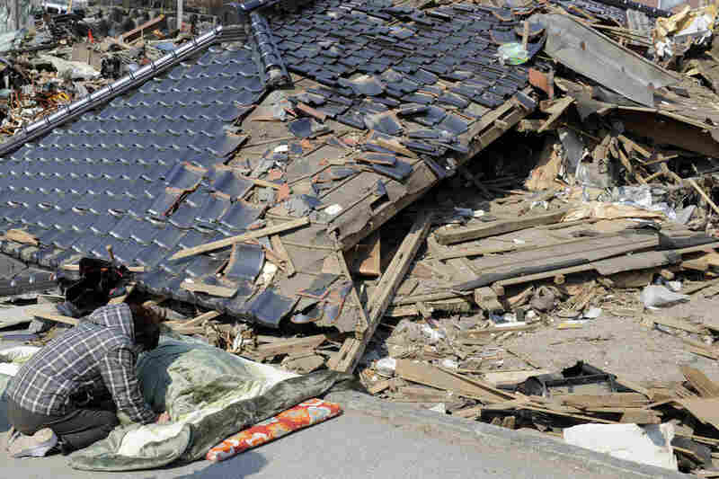 Akiko Murakami, 49, sits beside the body of her 85-year-old mother, Kotomi, found at her collapsed house in Rikuzentakata on Tuesday.